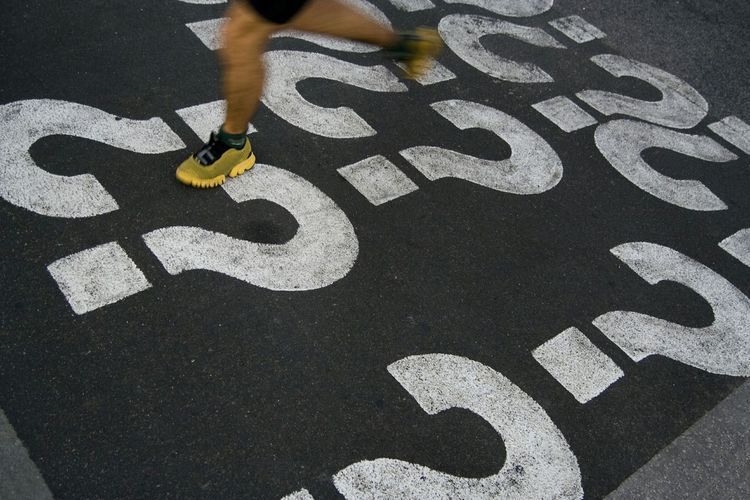 Low section of person running on street with question mark icons