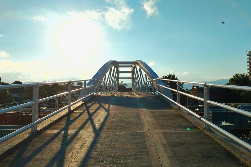 Footbridge against sky in city