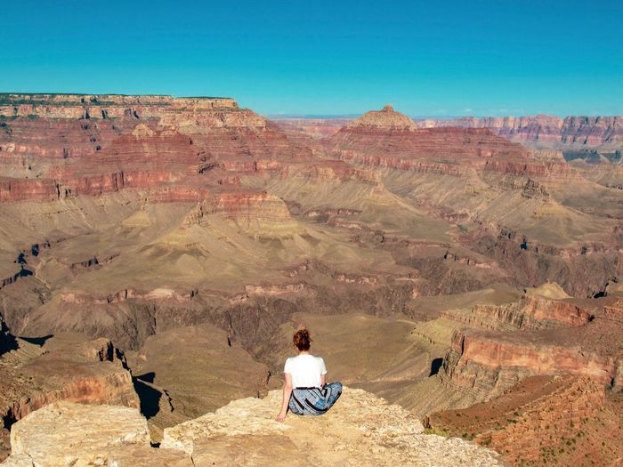 Reat view of woman sitting on rock admiring the  the view at grand canyon