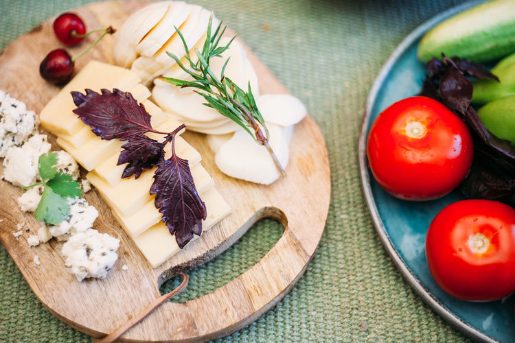 High angle view of cheese with vegetables on cutting board