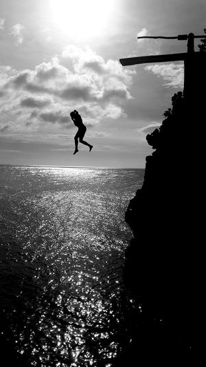 Silhouette woman jumping in sea from cliff
