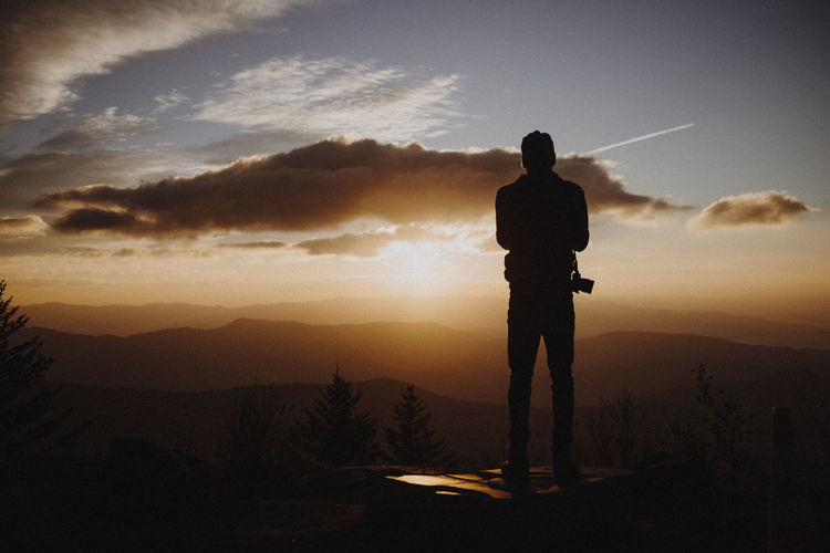 Silhouette man standing against sky at sunset