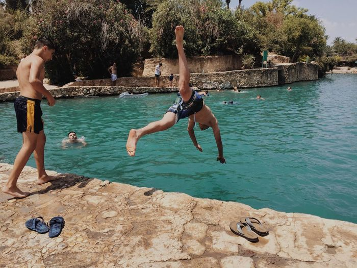 Jump Jumping Water Leisure Activity Mid-air Lifestyles Vacations Men Shirtless Person Swimwear Vitality Swimming Day Stone Material Nature People And Places Enjoy The New Normal מייסחנה My Year My View The Great Outdoors - 2017 EyeEm Awards