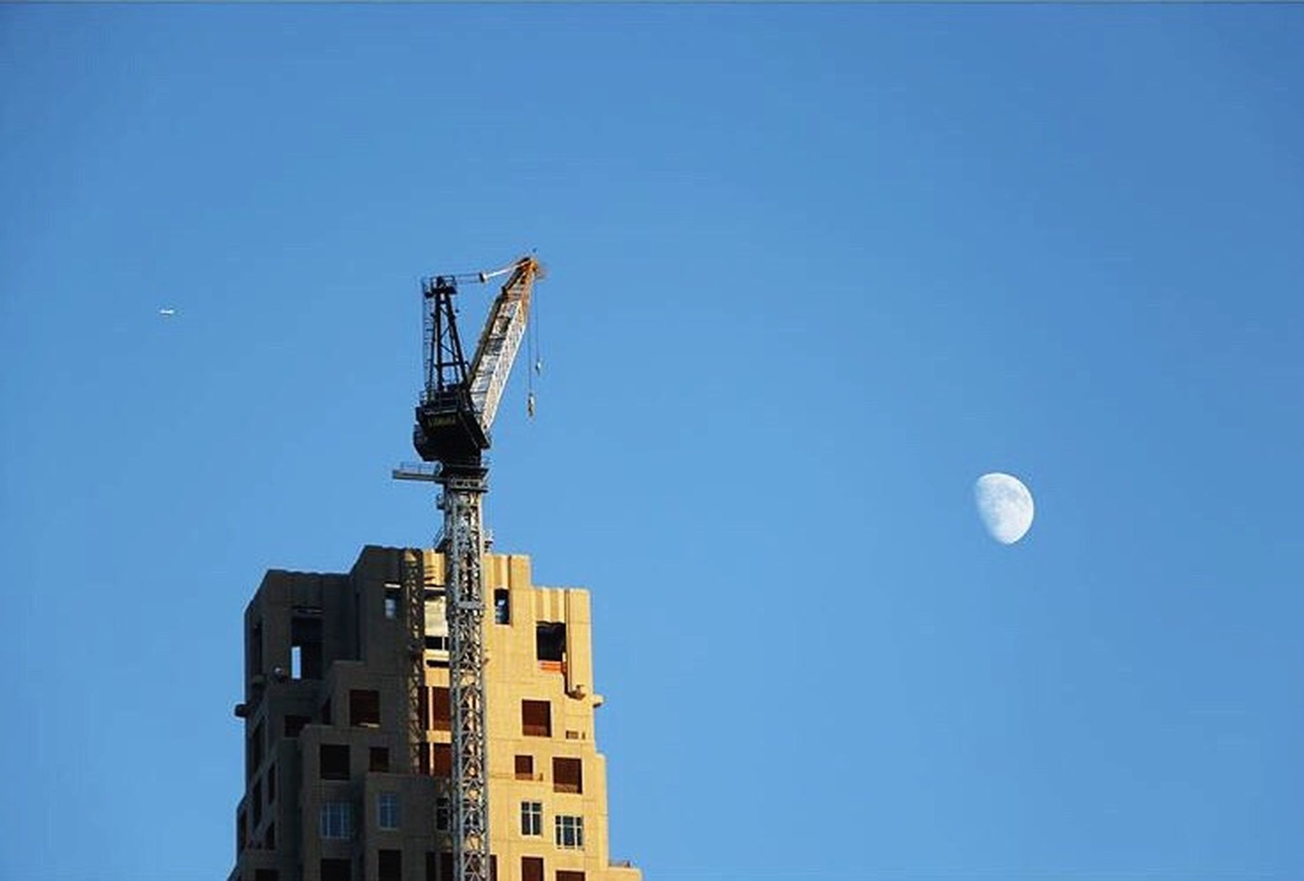 clear sky, low angle view, architecture, built structure, copy space, building exterior, blue, street light, moon, lighting equipment, city, outdoors, tower, building, high section, tall - high, no people, day, sky, crane - construction machinery