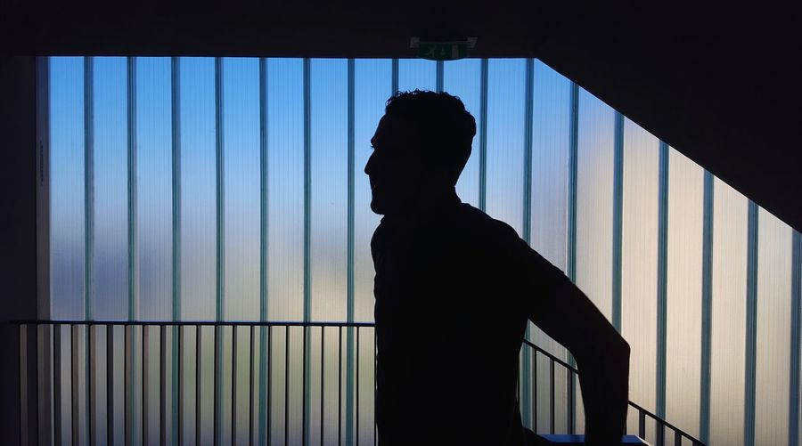 Silhouette Man Standing By Railing In Building