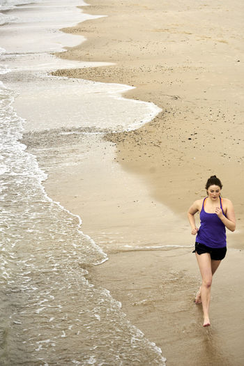Young Woman Running On Shore At Beach During Sunrise