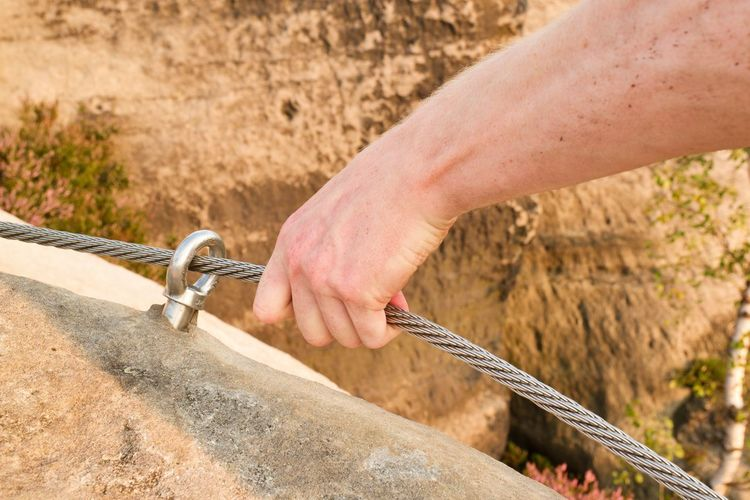 Rock climber's hand hold on steel rope at steel bolt eye anchored in sandstone rock via ferrata.