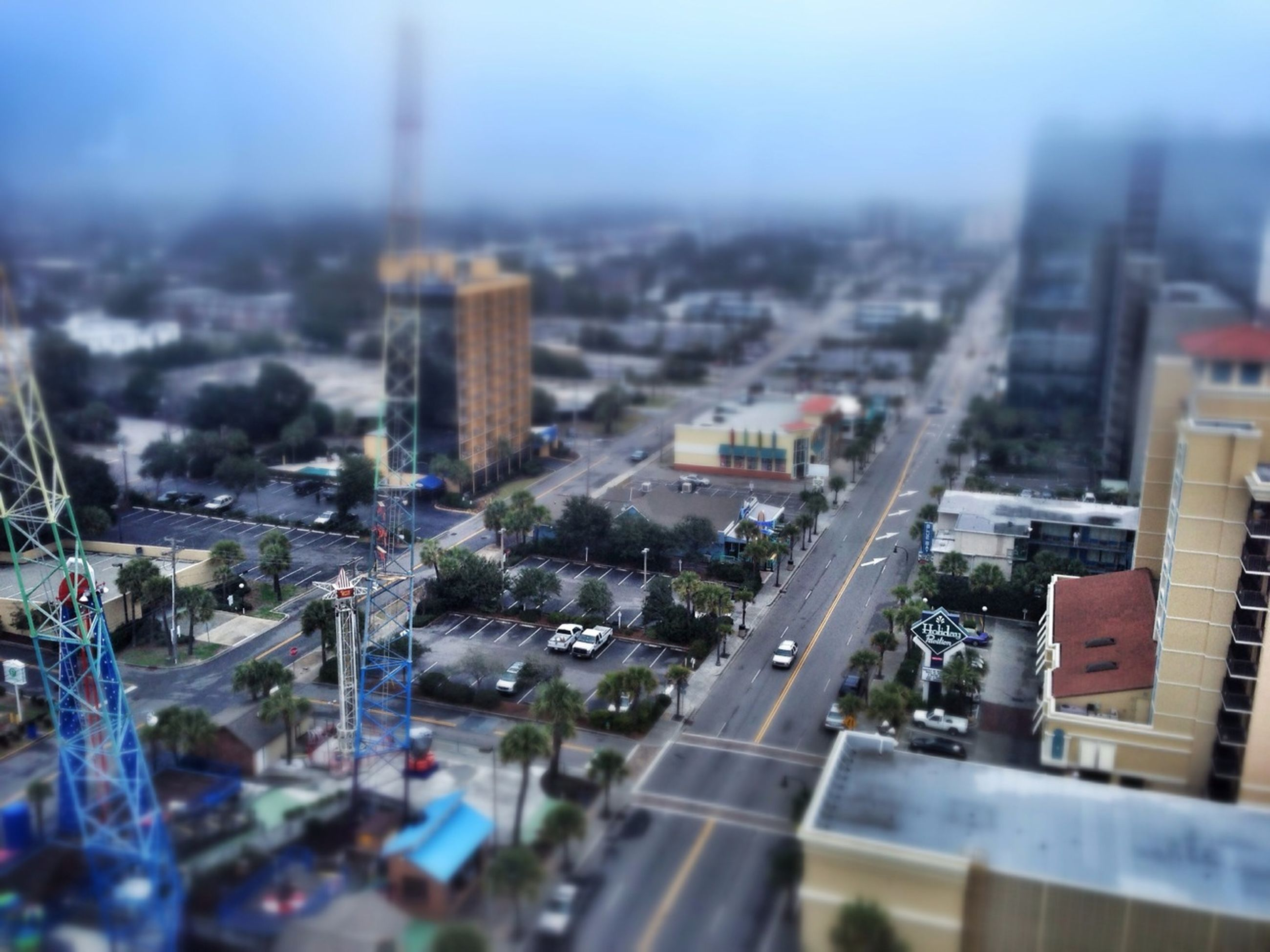 building exterior, architecture, city, cityscape, built structure, high angle view, transportation, crowded, residential district, road, sky, selective focus, residential building, city life, residential structure, car, street, day, focus on foreground, no people