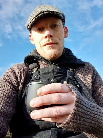 Portrait of man holding bottle against sky during winter
