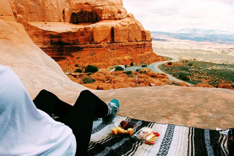 Low section of person sitting at arches national park