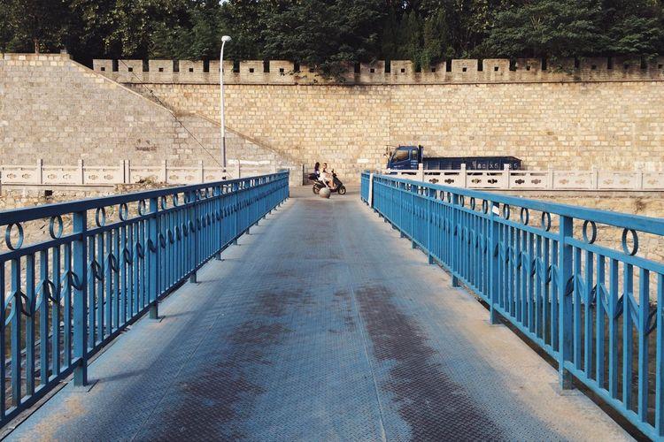 Metallic blue bridge against fortified wall