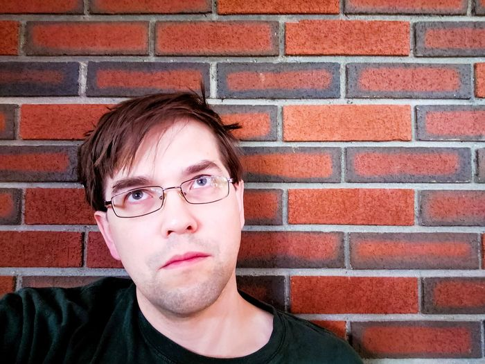 Portrait of a teenage boy against brick wall