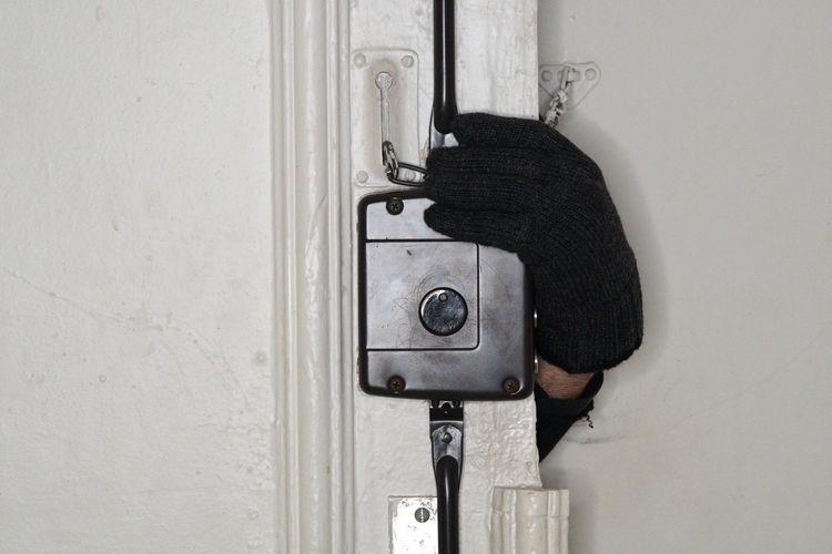 Cropped hand of thief opening door