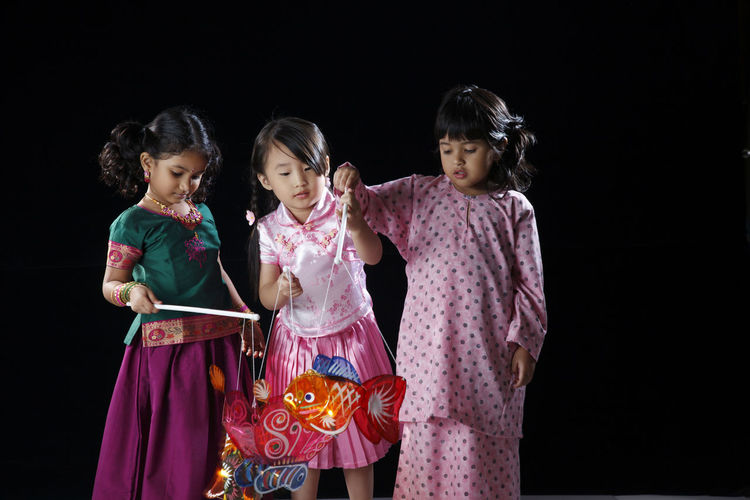 malaysia multi racial girls holding lantern Celebration Happiness Indian Lantern Traditional Clothing Black Background Child Childhood Chinese Flag Front View Group Of People Harmony Indoors  Innocence Lantern Festival Malay Ethnicity Malaysia Malaysian Mid Autumn Festival Multi Racial Sister Smiling Togetherness Women