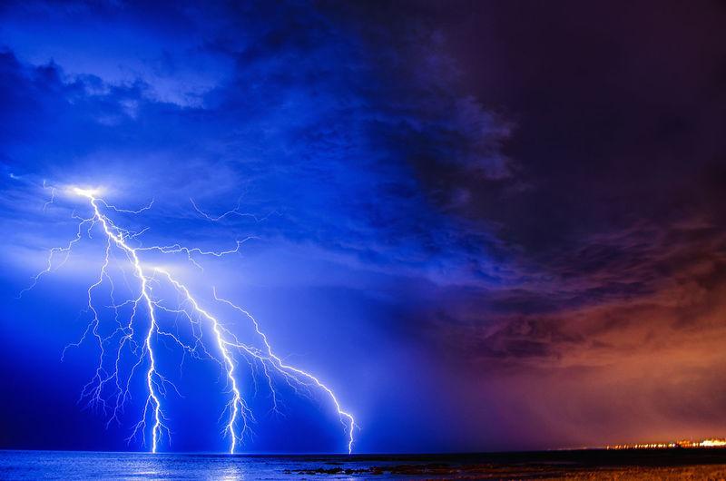 Lightning over sea against sky