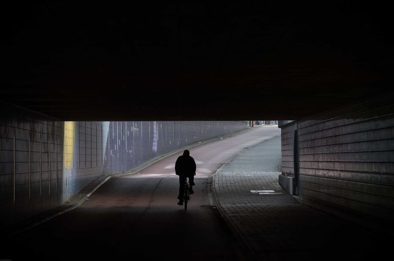 Silhouette Man Riding Bicycle In Tunnel