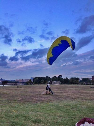Low angle view of person paragliding over field