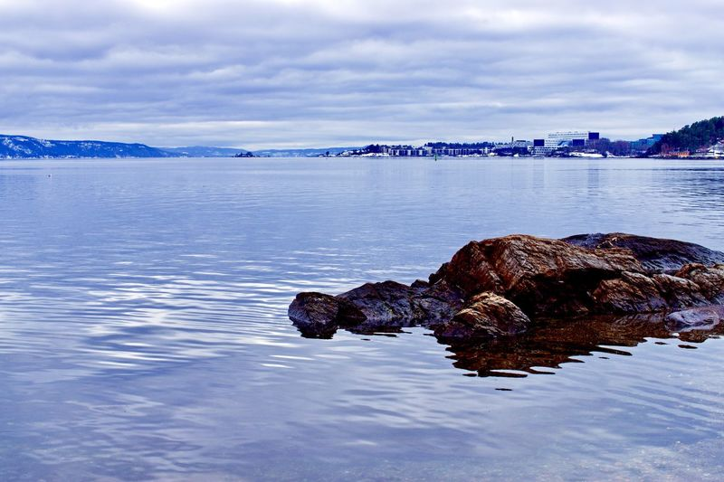 Clouds are mirrored in the Oslo fjord and the Equinor Building is seen in the distance Water Sky Cloud - Sky Tranquil Scene Sea Beauty In Nature Scenics - Nature Rock Waterfront Outdoors Idyllic Rock - Object Building Exterior Archive Statoil Equinor Vækerø Strand