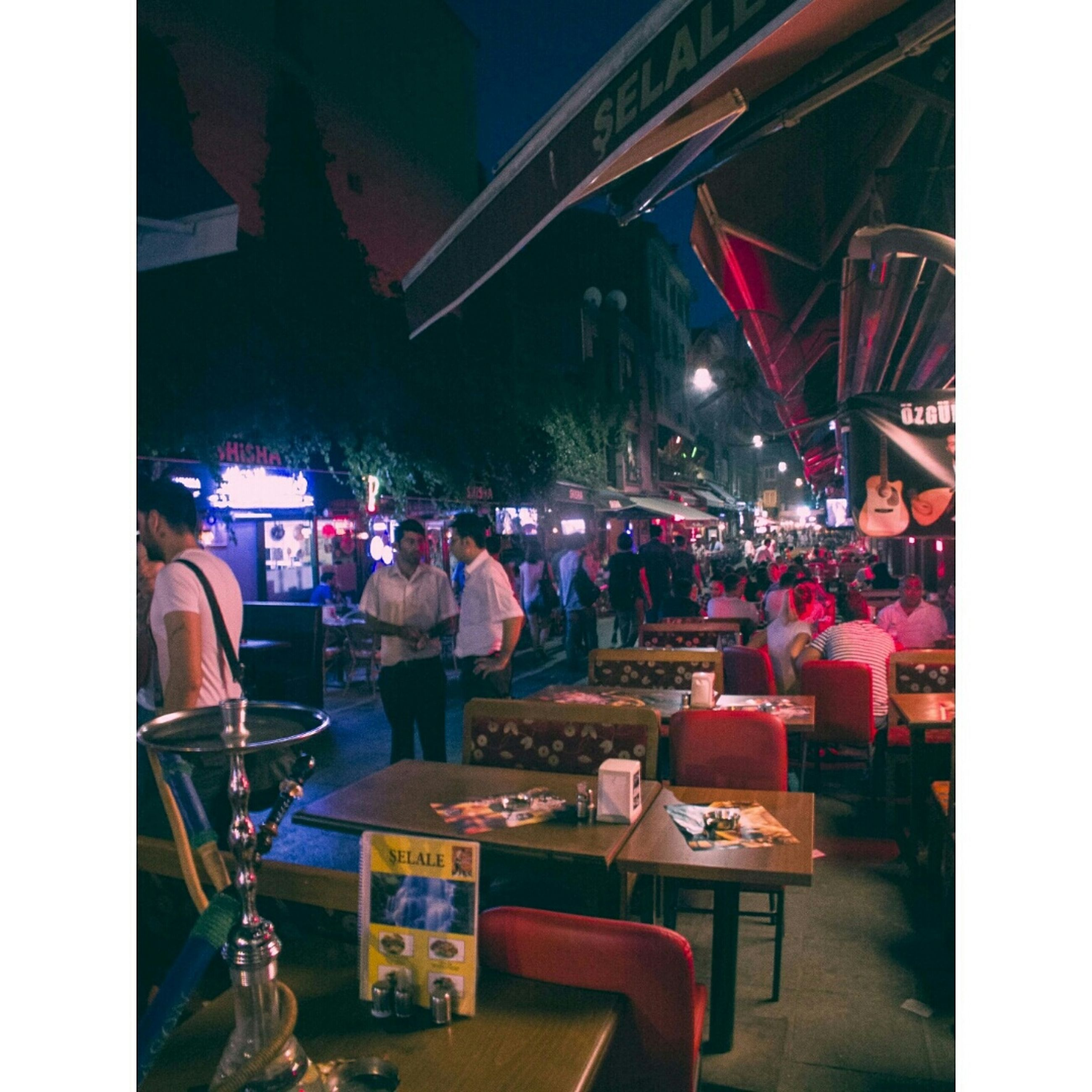 transfer print, auto post production filter, illuminated, night, transportation, chair, incidental people, built structure, mode of transport, indoors, architecture, table, building exterior, restaurant, land vehicle, street, city, person, sidewalk cafe