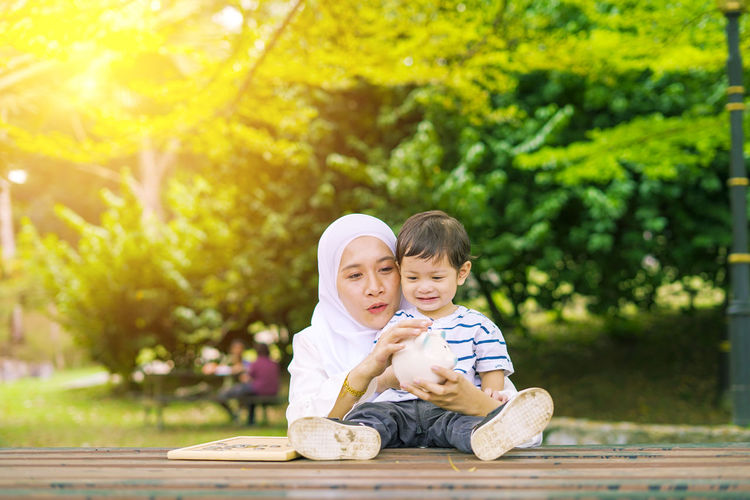Young woman with her cute son learn how to put coins into piggy bank. Future planning concept. Child Childhood Togetherness Family Males  Men Bonding Son Innocence Boys Two People Emotion Sitting Happiness Smiling Plant Adult Full Length Tree People Positive Emotion