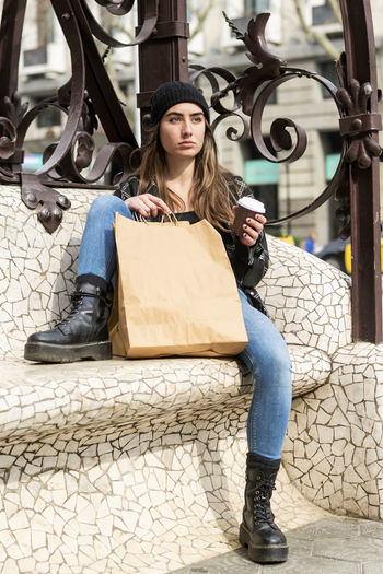 Full length of thoughtful woman with coffee cup and shopping bag sitting on bench at city