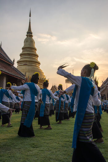 Women performing traditional dance by wat phra against sky during sunset