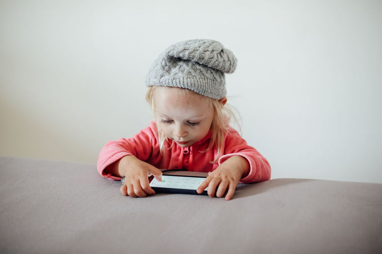Cute Girl Wearing Knit Hat Using Digital Tablet At Home