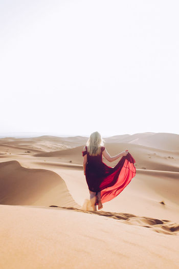 Young Woman Wearing Red Dress While Walking At Desert Against Clear Sky