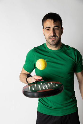 Portrait of young man holding ball against white background