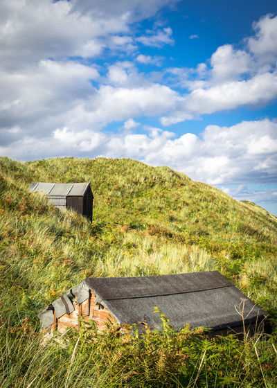 Huts on hill against cloudy sky