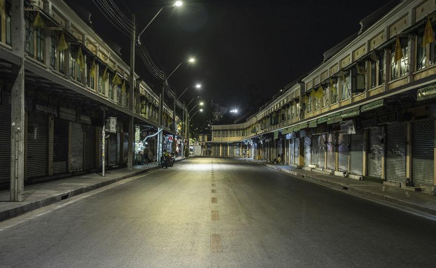 Empty road along illuminated buildings at night