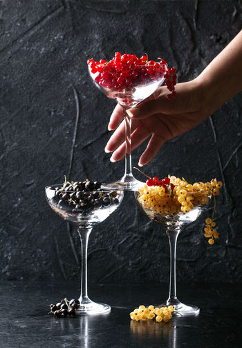 Cropped hand of woman stacking wineglasses with various currants