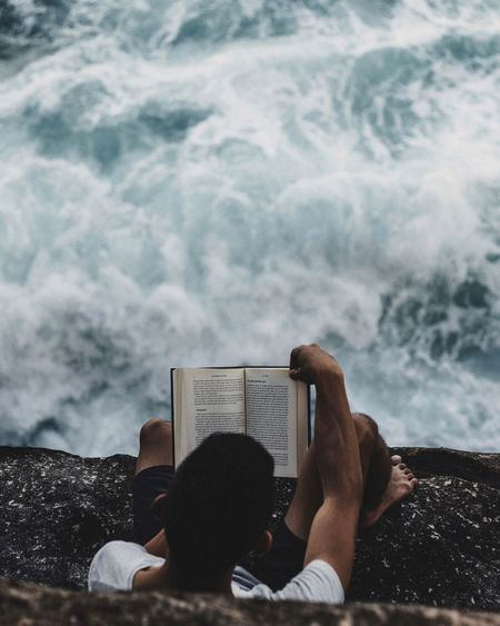 Directly above shot of man reading book while sitting on cliff against sea