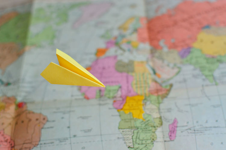 Close-up of yellow paper airplane flying over world map