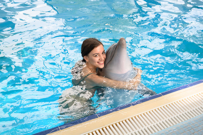 Portrait of smiling young woman with dolphin swimming in pool
