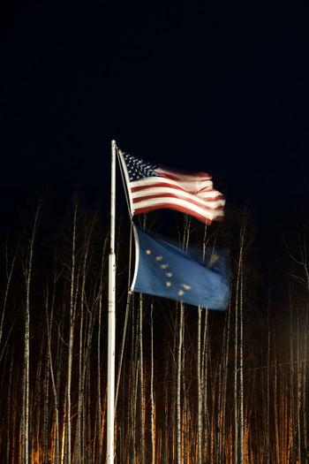 Illuminated flag against sky at night