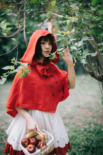 Woman in little red riding hood costume holding basket while standing by tree