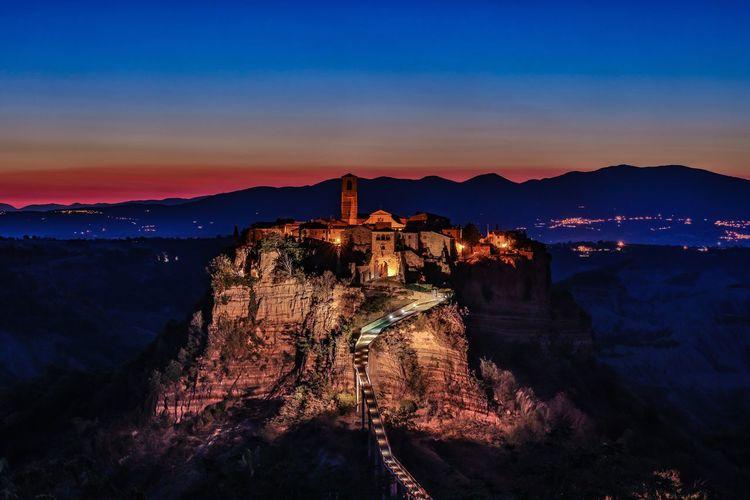 Illuminated Castle On Cliff During Sunset