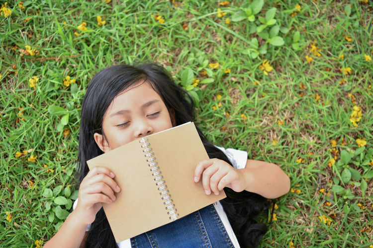 High Angle View Of Girl With Book Sleeping On Grassy Field At Park