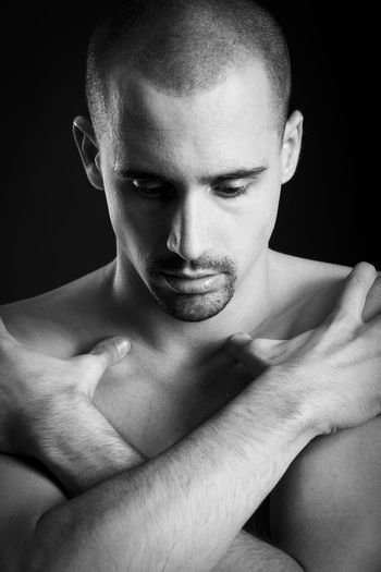 Thoughtful shirtless man covering chest with hands against black background