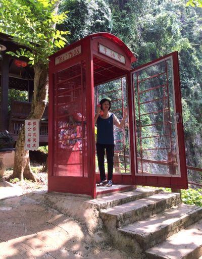 Red Telephone Booth Full Length Standing One Person Front View Real People Looking At Camera 2018 In One Photograph Casual Clothing Portrait Lifestyles Tree Day Built Structure Leisure Activity Architecture Plant Women Door Outdoors