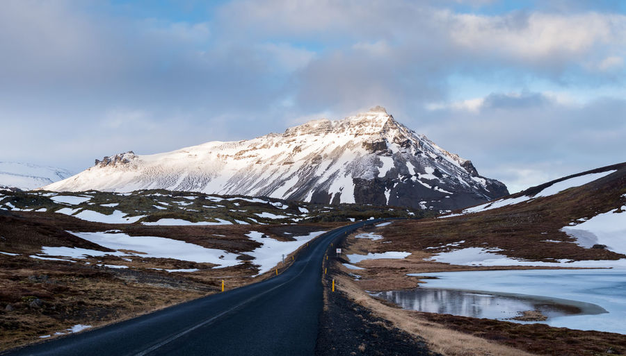 Typical icelandic snowy nature mountain landscape and empty road.
