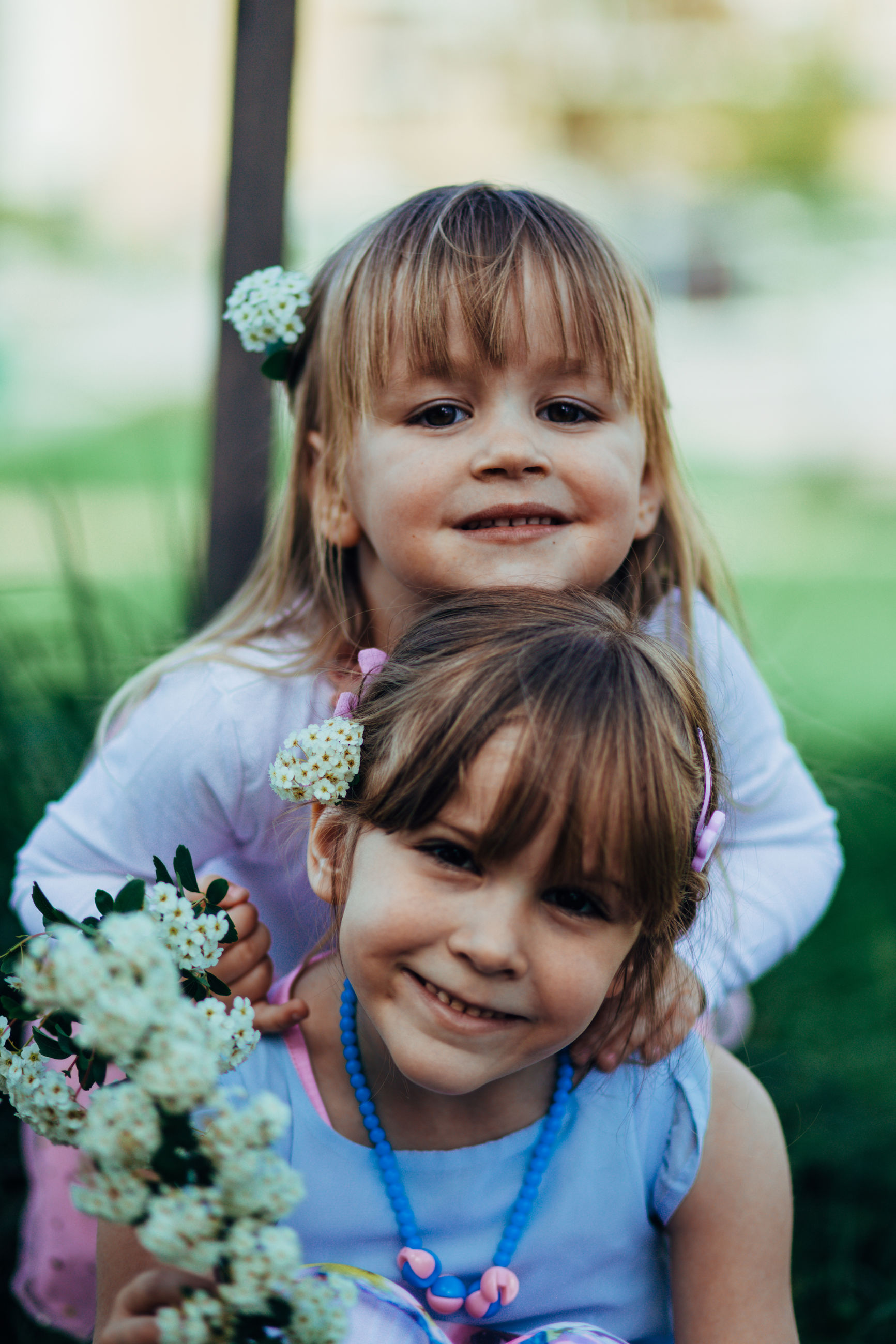 childhood, girls, real people, innocence, looking at camera, happiness, smiling, focus on foreground, togetherness, outdoors, day, cute, portrait, bangs, two people, bonding, leisure activity, front view, flower, elementary age, lifestyles, sitting, grass, nature, close-up, people