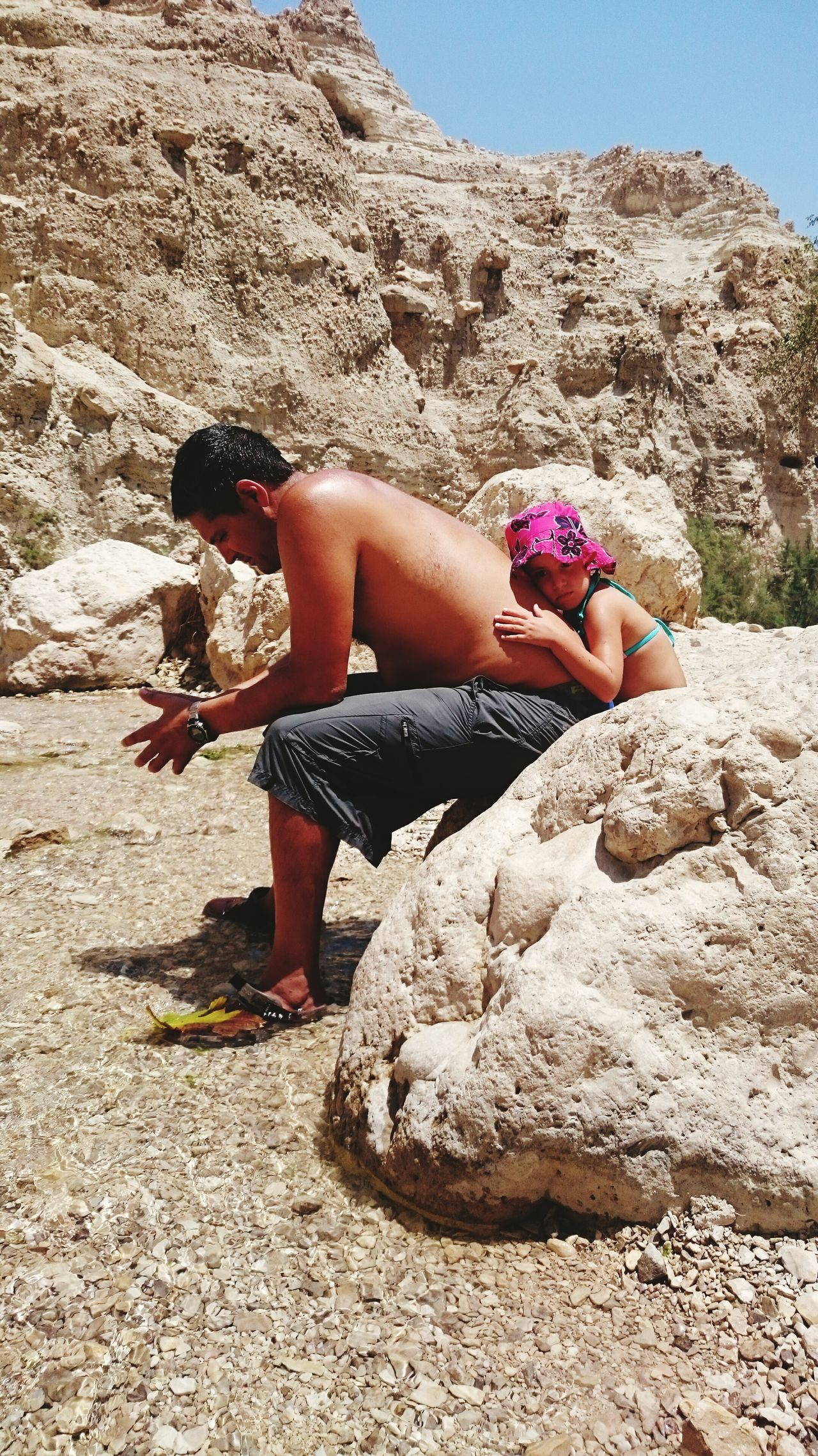 Daughter leaning over father while sitting on rock during sunny day