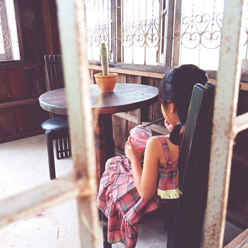 Rear view of girl having drink seen through window