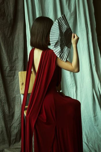 Fashion model holding hand fan while sitting on chair against curtains