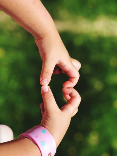 Cropped hands of child making heart shape