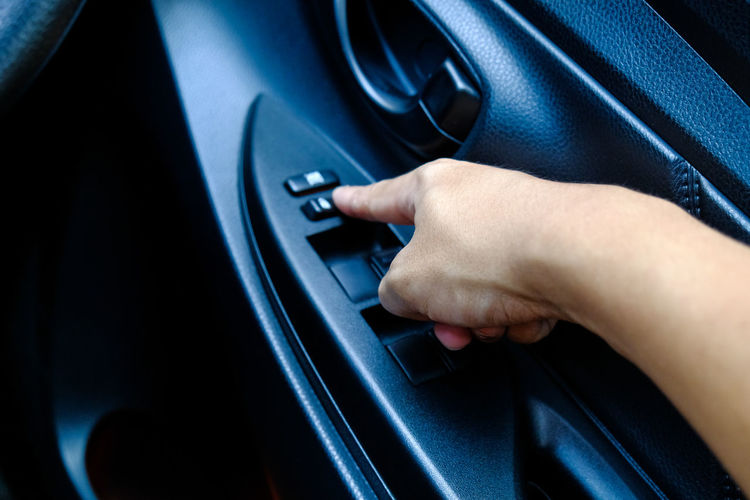 Cropped hand of person pressing button in car