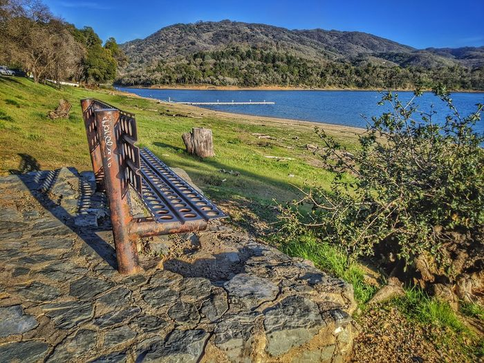 Scenic view of metal bench on stones against lake and mountains.