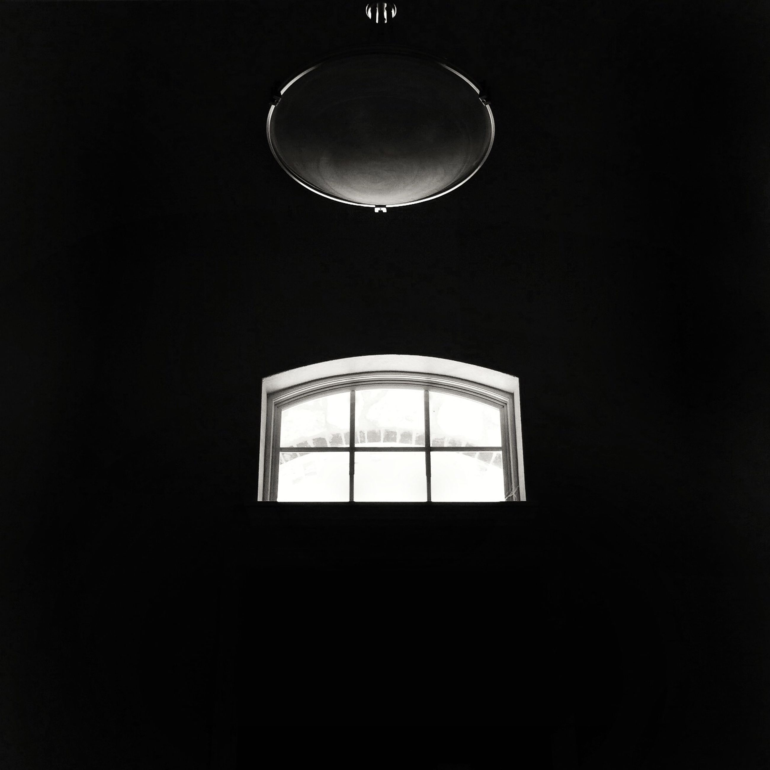 indoors, circle, copy space, glass - material, dark, illuminated, window, geometric shape, electricity, low angle view, transparent, lighting equipment, night, close-up, shape, built structure, architecture, no people, reflection, modern